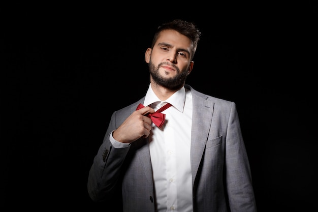 Young successful businessman taking off bowtie over black wall