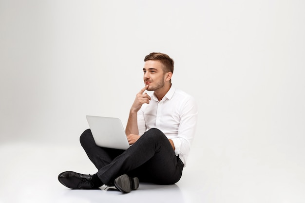 Young successful businessman thinking, sitting with laptop.
