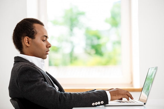 Young successful businessman typing on laptop, sitting at workplace