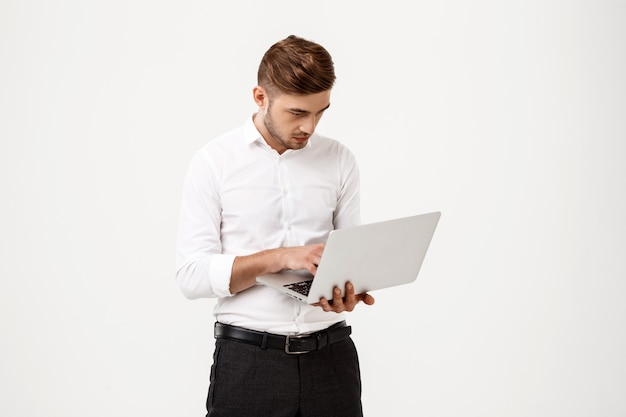 Young successful businessman typing on laptop.