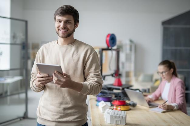 Молодой успешный бизнесмен, использующий тачпад с коллегой, серфингом в сети и заметками