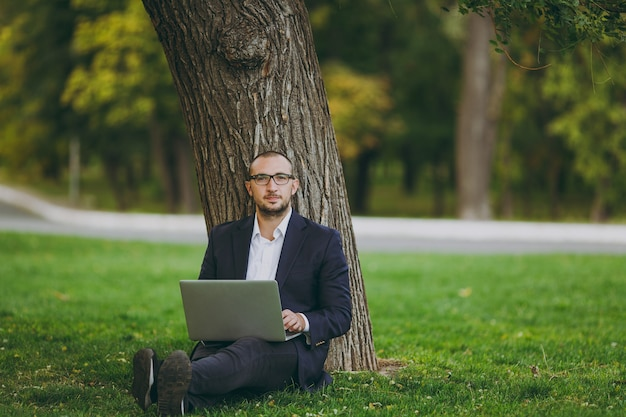 Young successful businessman in white shirt, classic suit, glasses. man sit on grass ground, work on laptop pc computer in city park on green lawn outdoors on nature. mobile office, business concept.