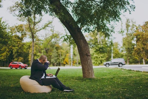 Giovane uomo d'affari di successo in camicia bianca, abito classico, occhiali. l'uomo si siede su un morbido pouf, lavorando su un computer portatile nel parco cittadino sul prato verde all'aperto sulla natura. ufficio mobile, concetto di affari.