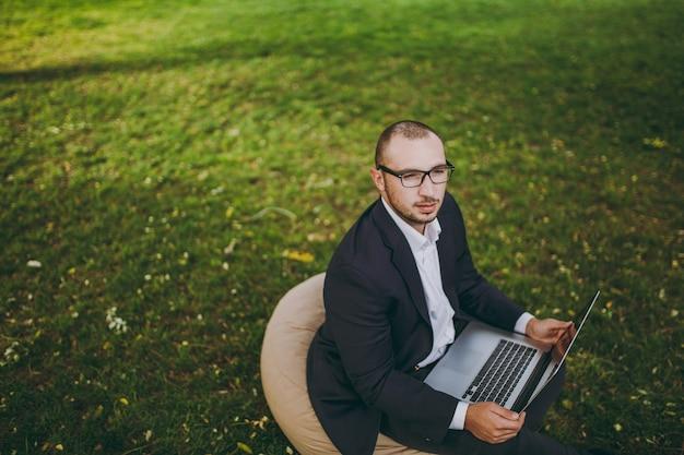 Giovane uomo d'affari di successo in camicia bianca, abito classico, occhiali. l'uomo si siede su un morbido pouf, lavorando su un computer portatile nel parco cittadino sul prato verde all'aperto sulla natura. concetto di ufficio mobile. vista dall'alto.