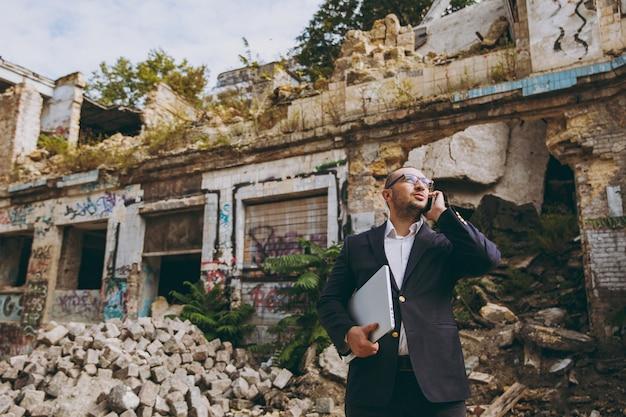Giovane uomo d'affari di successo in camicia bianca, abito classico, occhiali. uomo in piedi con un computer portatile, parlando al telefono vicino a rovine, detriti, edificio in pietra all'aperto. ufficio mobile, concetto di affari.