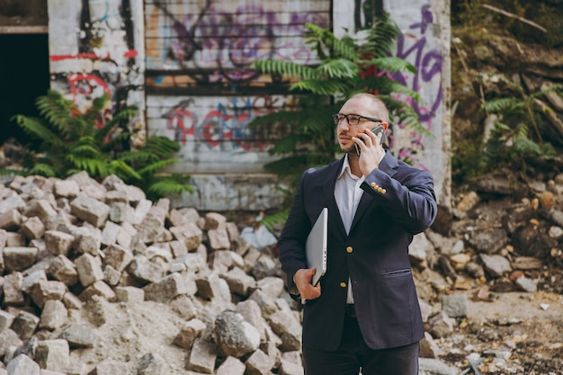 Young successful businessman in white shirt, classic suit, glasses. man standing with laptop pc computer, talking on phone near ruins, debris, stone building outdoors. mobile office, business concept.