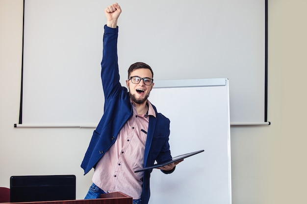 会議室の表彰台の後ろの白い画面に眼鏡とひげを持つ若い成功した実業家。