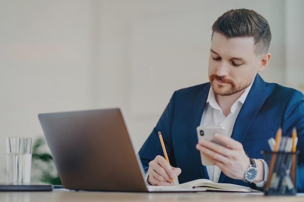Молодой успешный бизнесмен с мобильным телефоном в руке записывает важные данные в блокнот, сидя перед ноутбуком в офисе, одетый в стильный темно-синий деловой костюм и дорогие часы