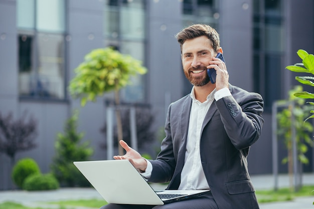 Young successful businessman working on laptop, bearded man in business suit looking at camera and smiling, talking on the phone near a modern office center outside