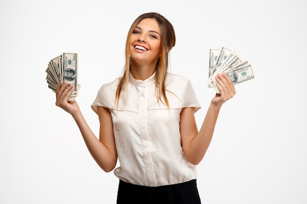Young successful businesswoman holding money over white background.