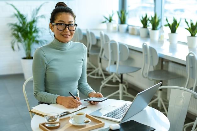 カフェのテーブルのそばに座って、ラップトップの前で作業し、メモをとるカジュアルウェアの若い成功した実業家
