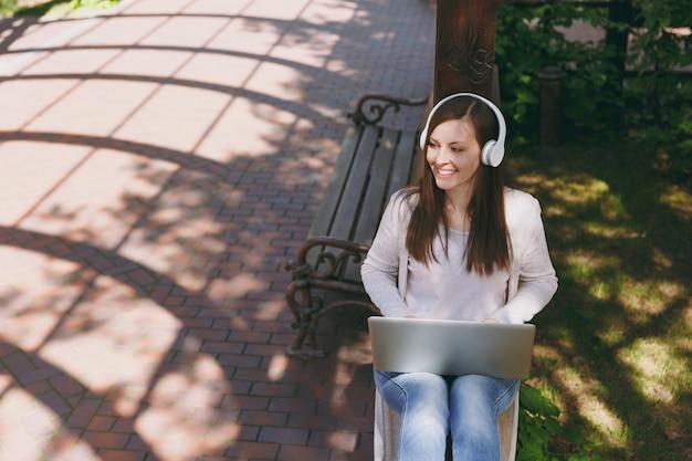 가벼운 캐주얼 옷을 입은 젊은 성공적인 사업가. 현대적인 노트북 pc 컴퓨터에서 일하는 여성은 야외 거리에서 헤드폰으로 음악을 듣습니다. 모바일 오피스. 프리랜서 비즈니스 개념입니다.