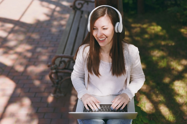 Young successful businesswoman in light casual clothes. woman working on modern laptop pc computer, listen music in headphones on head in street outdoors. mobile office. freelance business concept.