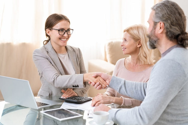 Young successful businesswoman looking at mature client while shaking his hand over table after signing contract