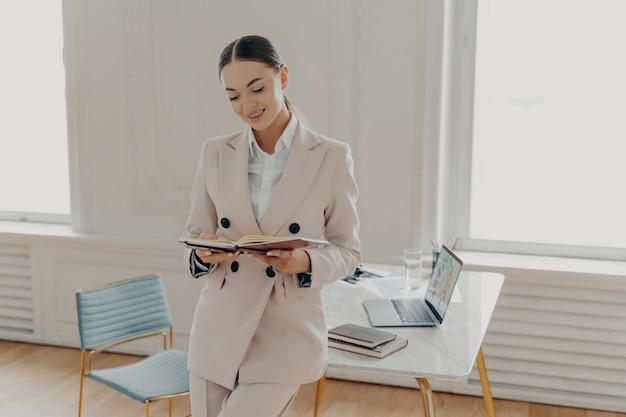 Молодой успешный бизнесмен в классическом бежевом костюме, глядя в блокнот со списком дел или бизнес-планом, стоя в офисном шкафу возле рабочего места. счастливый женский директор, планирующий рабочий день