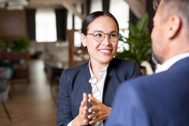 会議での会話中に彼女のビジネスパートナーを見てこぼれるような笑顔で若い成功した実業家