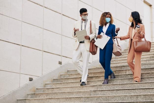 Молодые успешные бизнесмены в защитных масках спускаются по лестнице в офис и рассказывают о развитии недавнего проекта