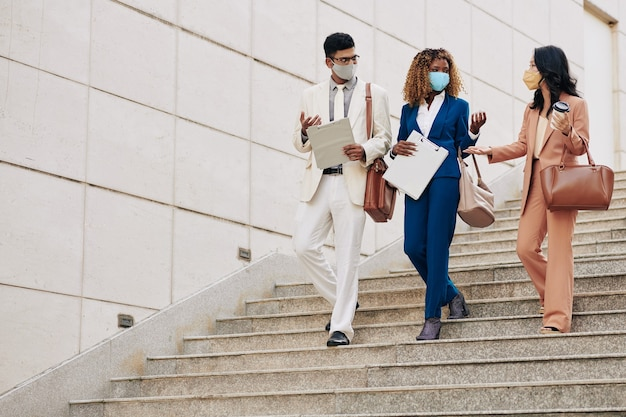 Young successful busness people in protective masks walking down stairs to office and talking about development of recent project