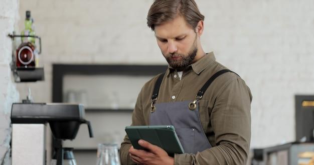 オンライン注文を受け付けている間、デジタルタブレットを使用して黒いエプロンを着てカフェに立っている若い成功したカフェの所有者。コーヒーショップのコンセプト。