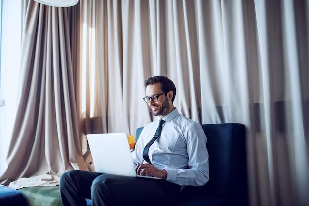 シャツとネクタイと彼のオフィスのソファーに座っているとラップトップを使用して眼鏡の若い成功した白人笑顔実業家。
