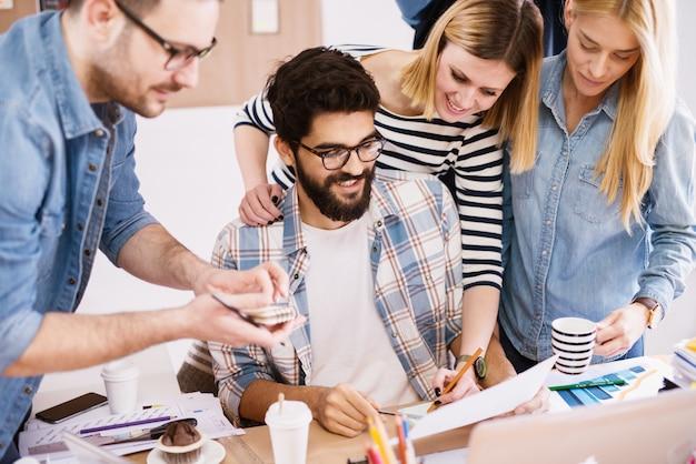 Молодые успешные, веселые и креативные деловые люди ищут анализ результатов своей работы