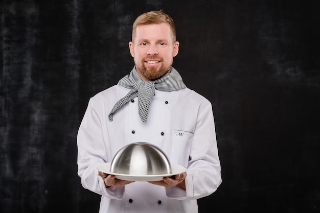 Молодой успешный шеф-повар в униформе держит клош с приготовленной едой, стоя на черном фоне