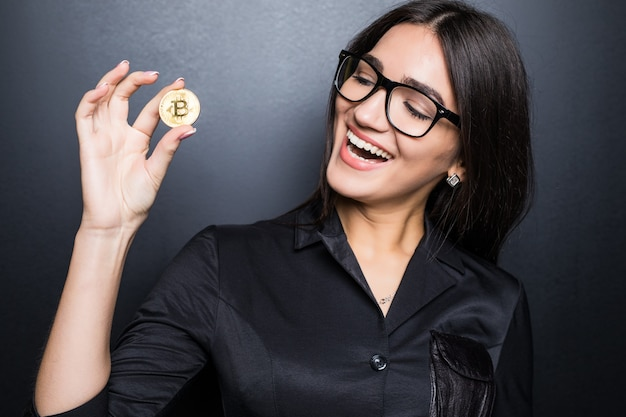 Молодая успешная уверенная в себе женщина в очках держит золотой биткойн в руке, изолированной на черной стене