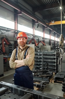 Young successful cross-armed engineer looking at you inside industrial plant