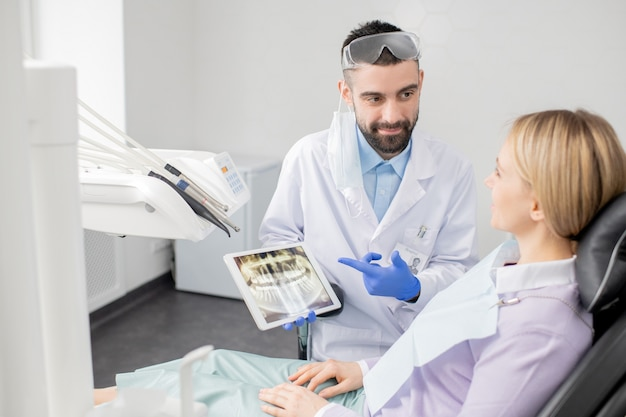 Young successful dentist in uniform pointing at touchscreen with teeth x-ray while showing his patient what should be done with it