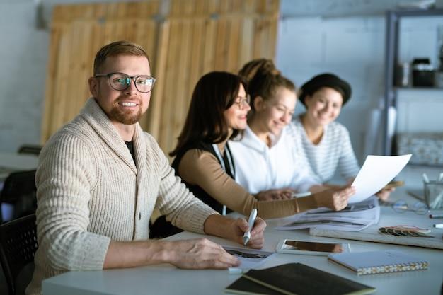 Молодой успешный дизайнер рисует новый модный эскиз на фоне коллег, просматривающих документы