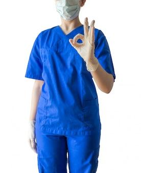 파란색 의료 제복을 입은 젊은 성공적인 여성 의사와 괜찮아 기호를 표시하는 마스크