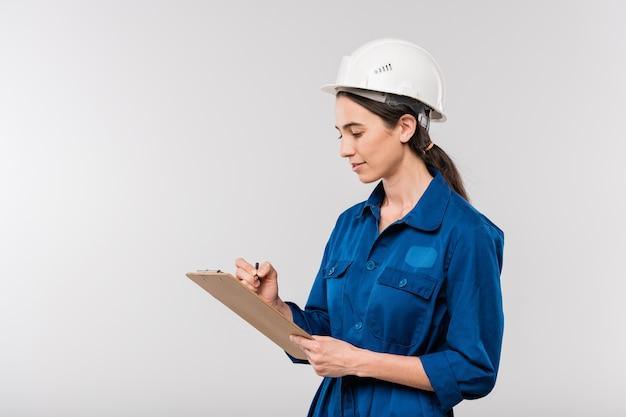 파란색 작업복 및 안전 헬멧에 젊은 성공적인 여성 엔지니어가 격리 된 문서에서 작업 메모를 작성