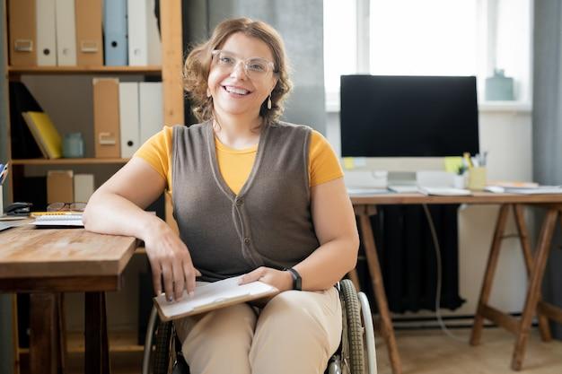 Молодая успешная женщина-офис-менеджер в инвалидной коляске, сидя за столом перед камерой, работая с документами или планируя работу