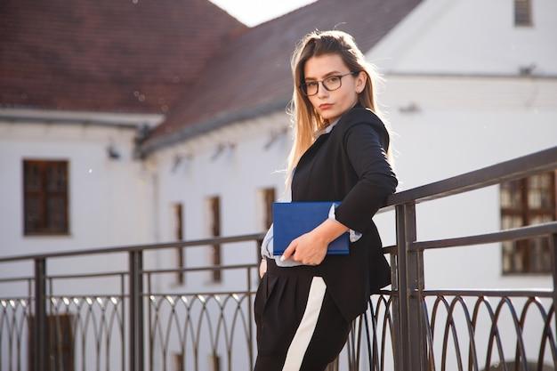 Молодая успешная внештатная девушка в костюме, очках с открытым ноутбуком.