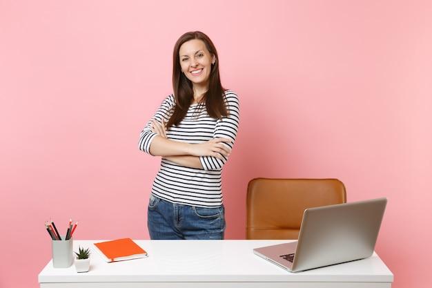 パステルピンクの背景に分離された現代的なpcのラップトップと白い机の近くに立ってカジュアルな服を着て若い成功した女の子。業績ビジネスキャリアコンセプト。広告用のスペースをコピーします。