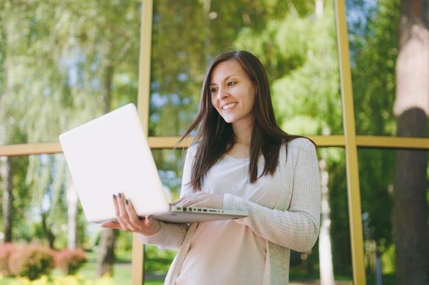 가벼운 캐주얼 옷을 입은 젊은 성공적인 소녀. 야외 거리에서 나무 반사와 거울 건물 근처 현대 노트북 pc 컴퓨터에서 작업 하는 미인. 모바일 오피스. 프리랜서 비즈니스 개념