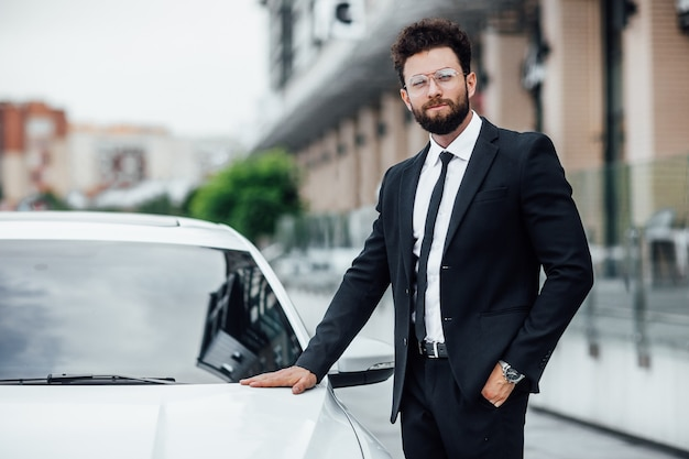 Young successful happy manager in black suit on the streets of the city with a white car near a modern business center