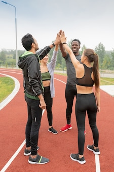 Young successful intercultural friends in sportswear touching by hands while standing in circle on outdoor stadium