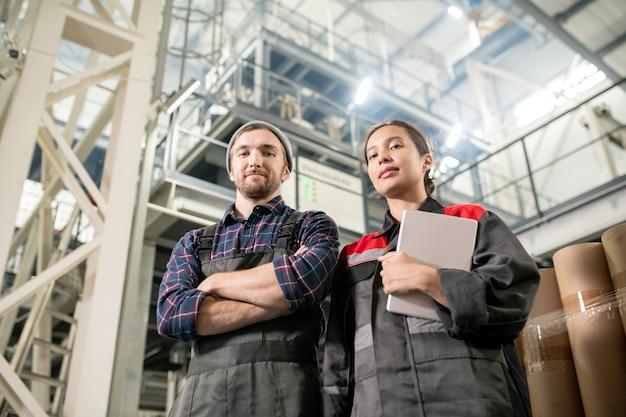 Молодые успешные инженеры мужского и женского пола на большом заводе стоят перед камерой и смотрят на вас на фоне огромного технического сооружения