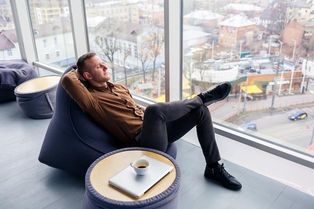 Молодой успешный бизнесмен мужского пола сидит возле большого окна в офисе и расслабляется. отдых после рабочего дня