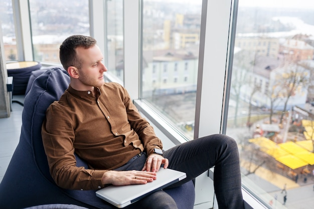Young successful male businessman sitting near a large window in the office and working at a laptop