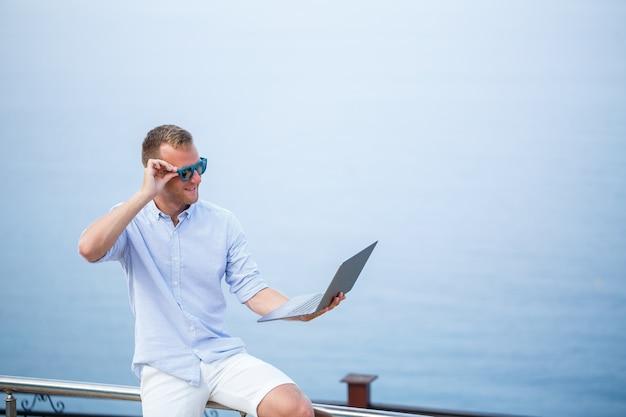 海のそばで休暇中にラップトップで作業する若い成功した男性実業家。彼はサングラス、シャツ、白いパンツを着ています。オフィスの外で働く、フリーランサー