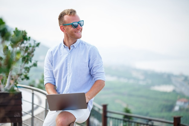 Young successful male businessman working with laptop on vacation by the sea. he wears sunglasses, a shirt and white shorts. work outside the office, freelancer