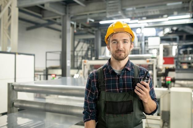 현대 공장의 대형 작업장에 서 있는 동안 워키토키를 사용하여 보호용 헬멧과 작업복을 입은 젊은 성공한 남성 엔지니어