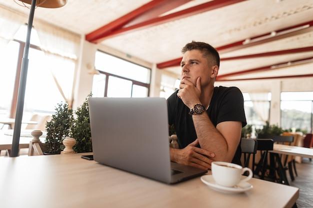 Молодой успешный человек в стильной одежде сидит за столиком в винтажном кафе с современным ноутбуком с чашкой кофе во время обеденного перерыва.