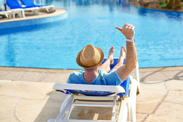 Young and successful man lying on a sun lounger at the hotel