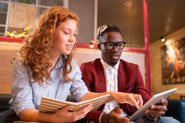 Молодые успешные мультикультурные студенты или сотрудники смотрят на сенсорную панель, а один из них указывает на экран