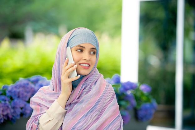 屋外で身も凍るようにしながらスマートフォンで誰かに相談するヒジャーブで若い成功したイスラム教徒の実業家