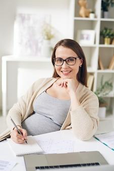 재무 그래프를 분석하고 홈 오피스에서 작업하는 동안 메모장에 메모를 작성하는 젊은 성공적인 임신 관리자