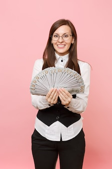 Young successful pretty business woman in glasses holding bundle lots of dollars, cash money isolated on pink background. lady boss. achievement career wealth concept. copy space for advertisement.